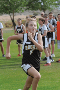Rocky Mountain seventh-grader Elsie Wassmer puts on a mighty kick as she nears the finish of the Lovell Invitational cross country meet Thursday at the Foster Gulch Golf Course. David Peck Photo
