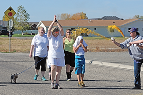 Brandy Tippetts throws colored corn starch on walkers participating in the fun run and walk to raise money for the Steven Muller family Saturday at the New Horizons Care Center. Receiving the burst of color are (l-r) Anna Atkinson, Suzanne Wilson, Mikayla Campbell and Maddie Campbell. David Peck photo