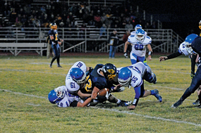 A trio of Lovell Bulldog defenders converge on Greybull running back Dawson McEwen during Friday night's hard-hitting 21-18 win by the Bulldogs in Greybull Friday night. Making the stop are (l-r) Jaret Collins, Kenneth Powell and Trace Murphey. Lovell hosts Thermopolis Friday at 7 p.m. in the first round of the playoffs. David Peck photo