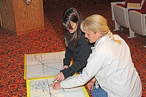 Aubrey Walker (left) and Jill Carpenter examine possible routes for a walking path in Lovell following the formal presentation by Christy Fleming at the community walking path meeting Thursday night at the Bighorn Canyon NRA Visitor Center. David Peck photo