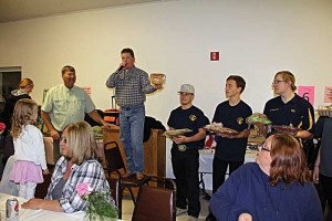Volunteer auctioneer Brett Oswood works to attract a good price for a baked good as emcee Mark Sorenson (left) looks on during the fundraiser for Lily Phillips Saturday evening in Deaver. Holding baked goodies to be on the auction block next are Rocky Mountain FFA members (l-r) Cole Boardman, Spencer Hedges and Chace Brand. In the foreground are Diane Wagner and Deidre Clendenen. Courtesy photo