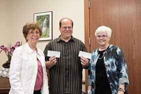 Jack Brinkerhoff (center) accepts donation checks from Lovell Woman's Club members Leslie McArthur (left) and Sylvia Crosby on behalf of Sylvia's sister Garnet Sorenson this week as a campaign kicks off to raise funds to replace the roof at the Hyart Theatre.  Patti Carpenter photo