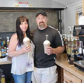 Krystal and Bill Pulver each hold an Ice Rage frosty drink in their new Happily Grounded coffee stand this week. The new business on East Main in Lovell features more than 60 flavors of Italian sodas, smoothies, coffees and other drinks. David Peck photo