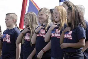 Lovell Elementary School students (l-r) Maddie Felkins, Maycee Jones, Kallie Owens and Erminia Garcia perform a patriotic song during the Memorial Day celebration held at the Lovell Cemetery on Monday.