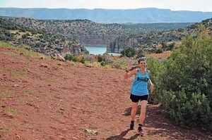 Racing Turtles team member Michelle Croft of Lovell cruises along the Barry's Island trail during the third state of the Bighorn Canyon Triathlon Saturday. This year's triathlon featured spectacular views of the lake and canyon. David Peck photo