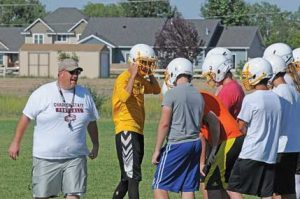 New head football coach Richard Despain encourages his Rocky Mountain football squad during a workout Tuesday morning on the practice field in Cowley. David Peck photo