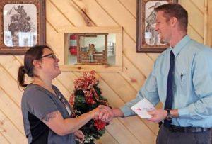 Lovell Area Chamber of Commerce President Joseph Shumway presents the chamber's customer service award to North Big Horn Hospital employee Jenna VanKirk on Monday at the Brandin' Iron Restaurant in Lovell. Patti Carpenter photo
